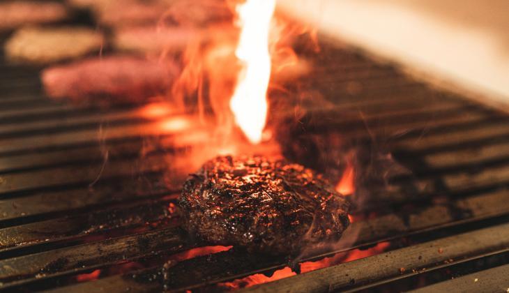 Hamburguesa en la parrilla con llamas de fondo