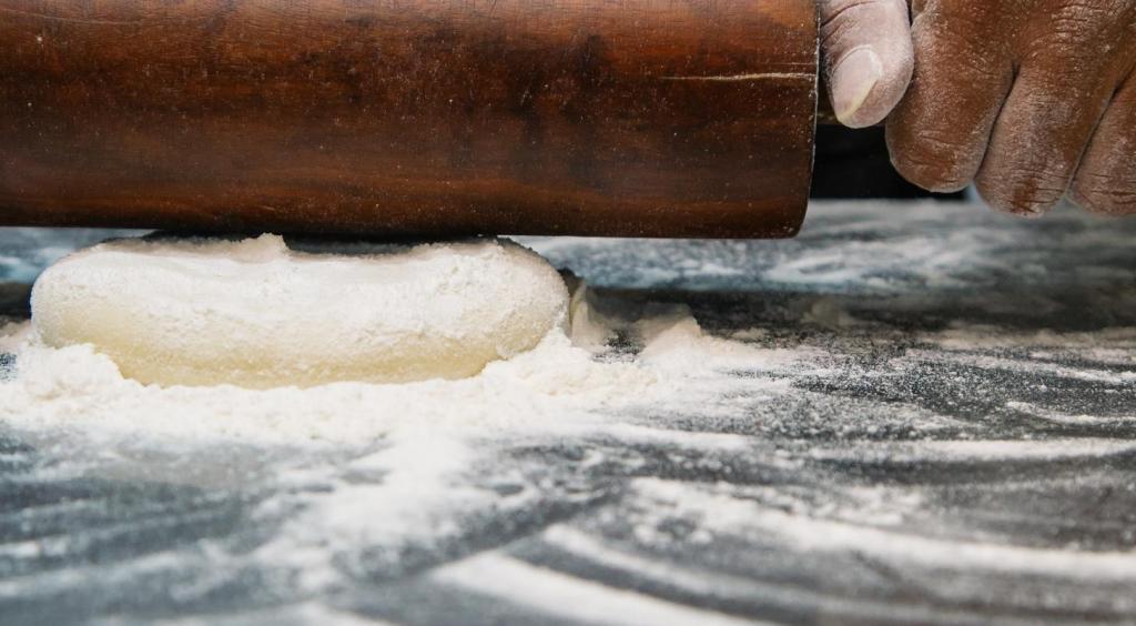 Manos amasando con un rodillo una masa sobre mesa llena de harina