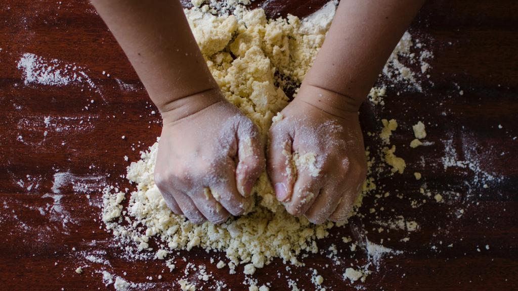 Manos de una persona mezclando y amasando para hacer pan