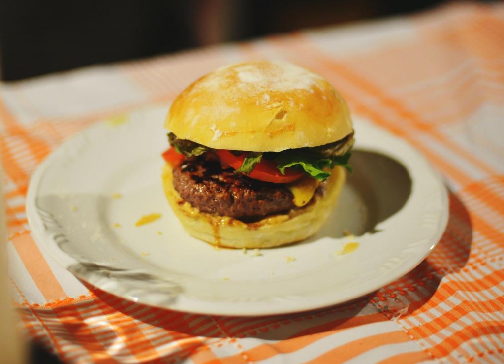 Fotografía de hamburguesa clásica americana estilo casero sobre un plato blanco y un mantel naranja de rayas
