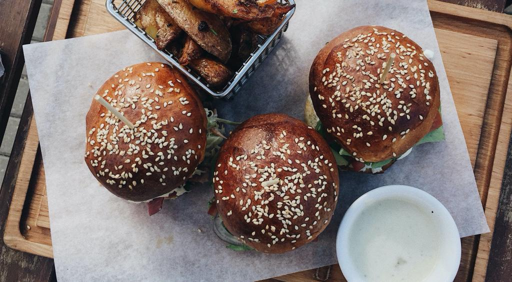 Varias hamburguesas vistas desde arriba sobre una bandeja de madera, junto a un cuenco con salsa y una cesta con patatas fritas
