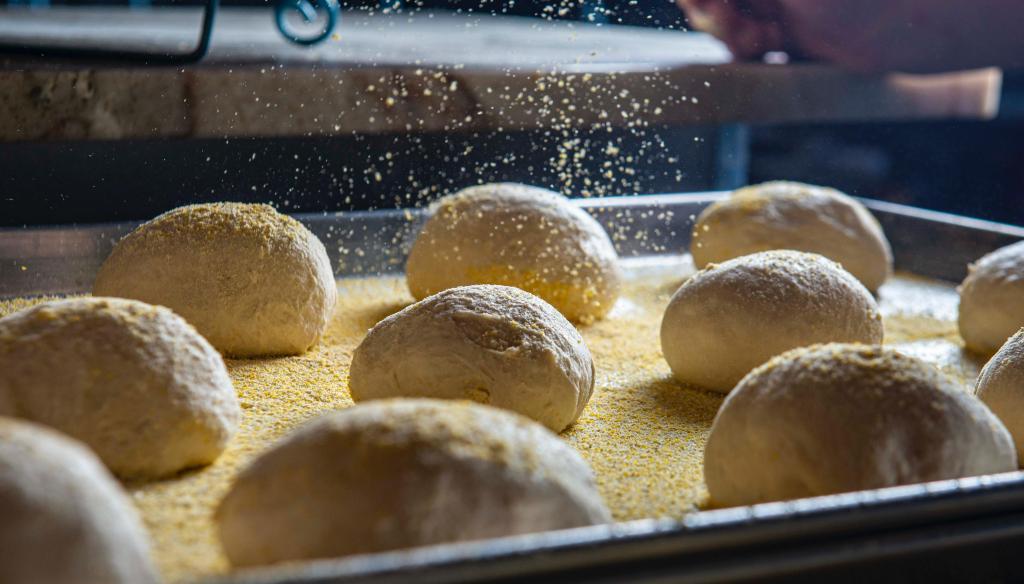 Varias porciones de masa sobre bandeja de horno siendo espolvoreada por encima con semillas