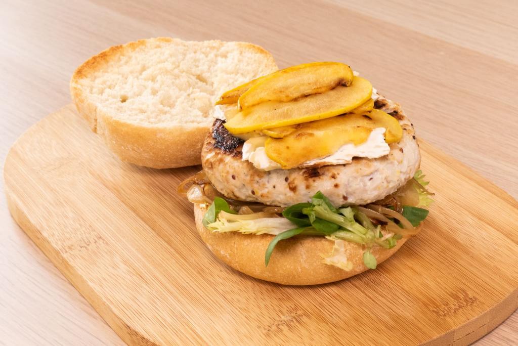 Imagen de hamburguesa de pollo con manzana asada, queso camembert fundido sobre una cama de cebolla pochada y mix de lechugas