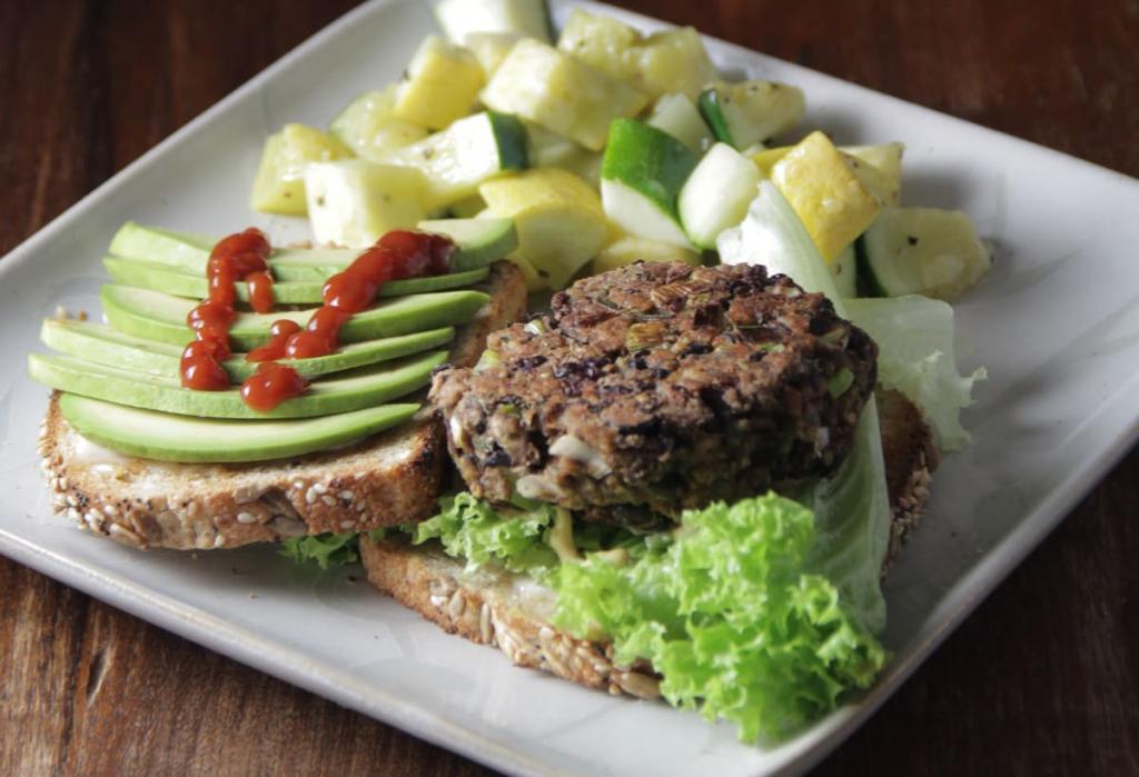 Hamburguesa de legumbres con lechuga y aguacate emplatada con guarnición de mix de verduras asadas