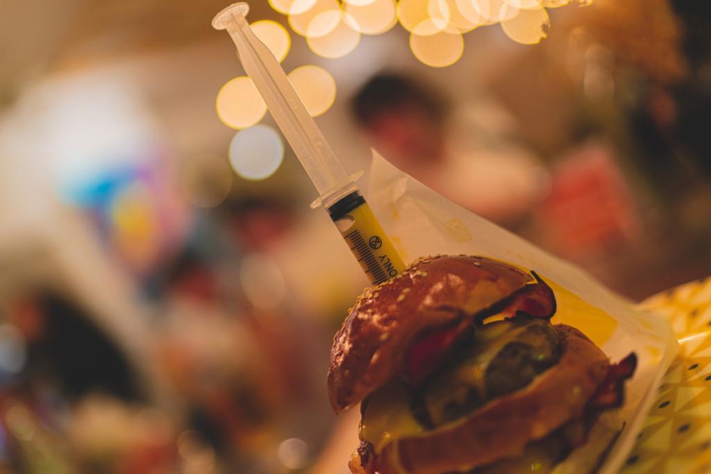 vista de una hamburguesa con fondo desenfocado, en la que hay clavada una jeringuilla con queso