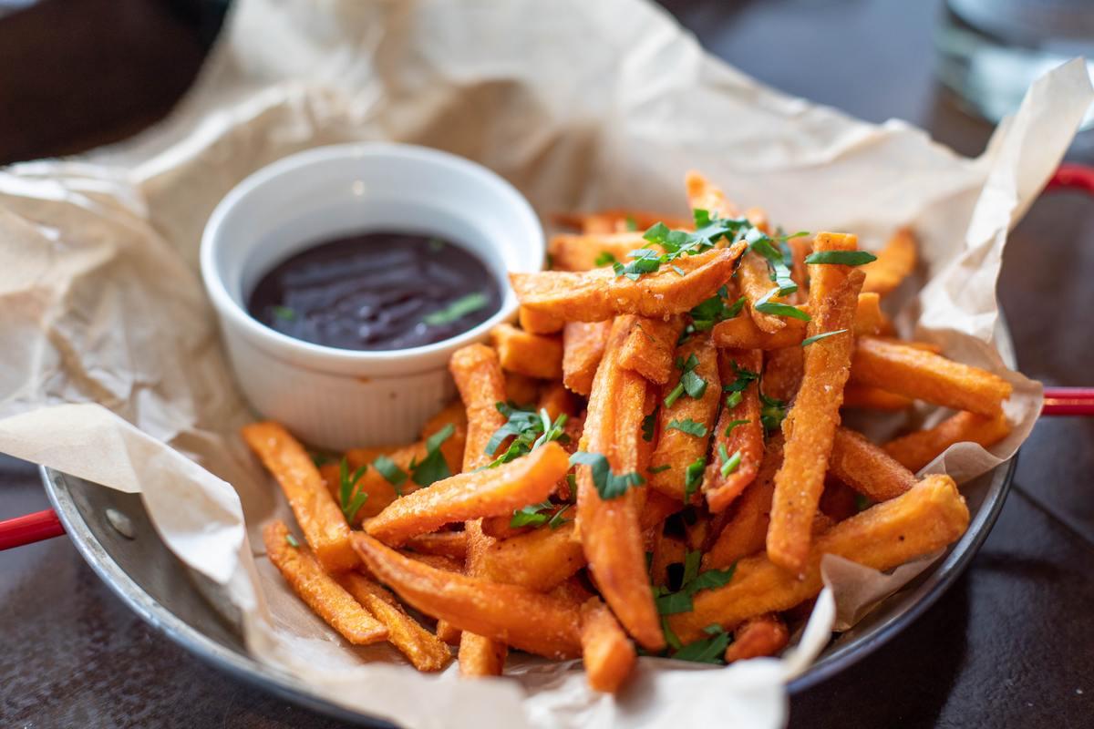 Plato de palitos de boniato fritos con perejil espolvoreado encima y un pequeño cuenco de salsa